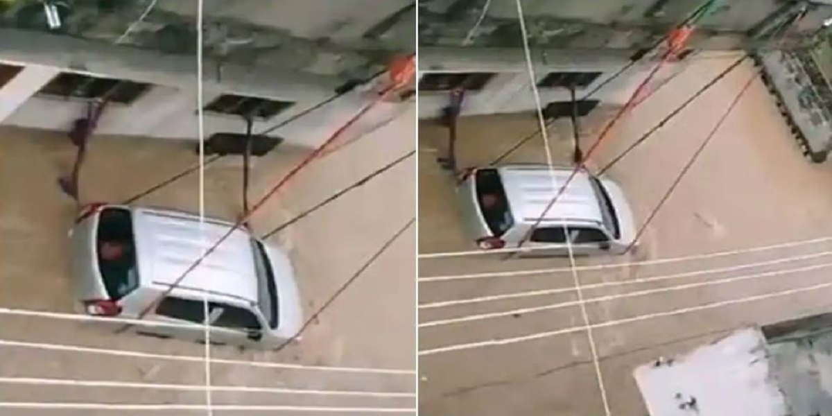 Footage of a car tied with rope to keep it from being in floodwater