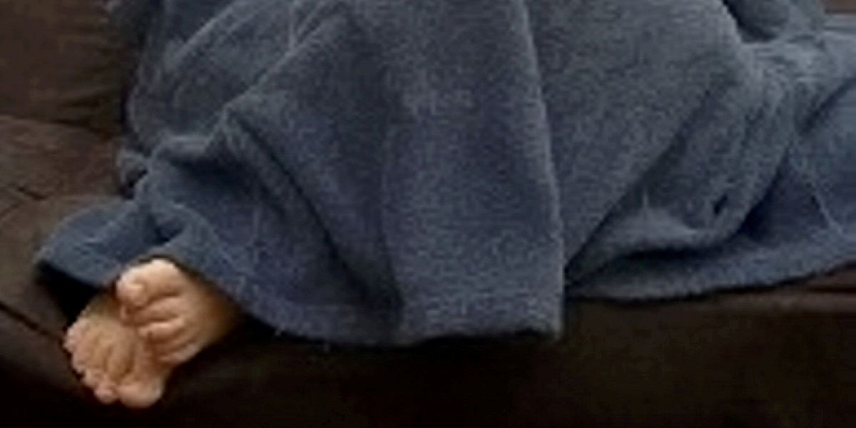 A wanted guy is discovered hiding under a blanket with his feet protruding