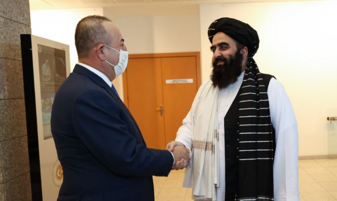 Turkish Foreign Minister Mevlut Cavusoglu (L) shakes hands with Afghanistan's acting Foreign Minister Amir Khan Muttaqi in Ankara